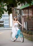Милая маленькая девочка в белого катания платья винтажной велосипеда улице города вниз старой исторической Стоковые Фотографии RF