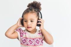 Милая маленькая девочка в красочном платье слушая музыку с наушниками на белой предпосылке стоковая фотография rf