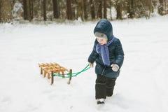 Милая маленькая девочка в лесе на холодный зимний день с скелетоном Стоковое фото RF