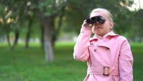 Милая маленькая девочка в пинке используя бинокли в парке видеоматериал