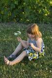 Милая маленькая девочка в платье лета сидя в лужайке в свете позднего вечера золотом Стоковые Фотографии RF