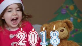 Милая маленькая девочка в шляпе Санта Клауса дуя вне свечи - съемка крупного плана схематический знак 2018 сток-видео