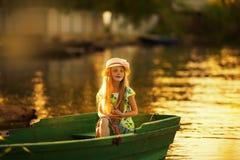 Милая маленькая девочка в шляпе сидя в шлюпке на озере на заходе солнца Стоковое Фото