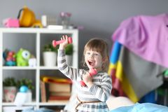 Милая маленькая девочка делает физические упражнения дома стоковое фото rf
