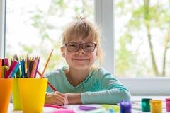 Милая маленькая девочка делая домашнюю работу, читающ книгу, крася страницы, сочинительство и картину Краска детей Притяжка детей стоковое фото