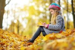 Милая маленькая девочка делая эскиз к снаружи на красивый день осени Счастливый ребенок играя в парке осени Чертеж малыша с цвета стоковое фото