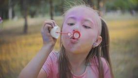 Милая маленькая девочка дует пузыри мыла в саде outdoors на солнечный день движение медленное акции видеоматериалы