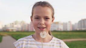 Милая маленькая девочка дуя на одуванчике и усмехаясь на городской лужайке сток-видео
