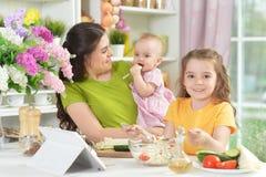 Милая маленькая девочка есть свежий салат на кухонном столе Стоковая Фотография RF