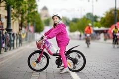 Милая маленькая девочка ехать велосипед в шлеме города нося на летний день Стоковые Фото