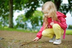 Милая маленькая девочка играя в лужице на красивый летний день outdoors Стоковая Фотография RF