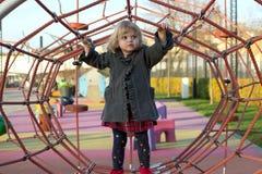 Милая маленькая девочка играя на спортивной площадке стоковые изображения rf