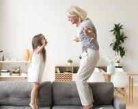 Милая маленькая девочка играя с бабушкой скача на toget кресла стоковые фото