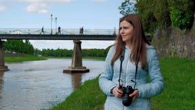 Милая маленькая девочка идет вдоль портового района и фото принимать с профессиональной камерой Мост и стена года сбора винограда акции видеоматериалы