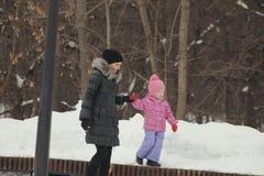 Милая маленькая девочка идя с ее матерью на улице зимы, дочь ломая вне и идя независимо Стоковое Изображение RF