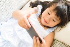 Милая маленькая девочка имея потеху для того чтобы сыграть игру на умном телефоне стоковые фотографии rf