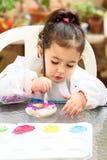 Милая маленькая девочка имея потеху, красящ с щеткой, игрой и красить Preschooler с краской на саде стоковые фото