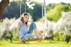Милая маленькая девочка имея потеху на качании в blossoming старом саде яблони outdoors на солнечный весенний день стоковые изображения