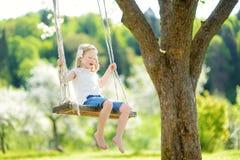 Милая маленькая девочка имея потеху на качании в blossoming старом саде яблони outdoors на солнечный весенний день стоковые фотографии rf
