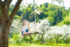 Милая маленькая девочка имея потеху на качании в blossoming старом саде яблони outdoors на солнечный весенний день стоковые изображения rf