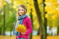 Милая маленькая девочка имея потеху на красивый день осени Счастливый ребенок играя в парке осени Ребенк собирая желтый листопад стоковое изображение