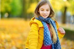 Милая маленькая девочка имея потеху на красивый день осени Счастливый ребенок играя в парке осени Ребенк собирая желтый листопад стоковые изображения rf