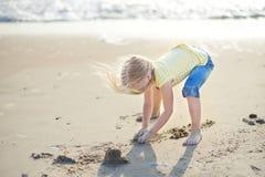 Милая маленькая девочка имея потеху на песчаном пляже на теплый и солнечный летний день Ребенк играя океаном Стоковая Фотография RF