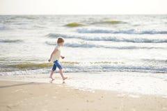 Милая маленькая девочка имея потеху на песчаном пляже на теплый и солнечный летний день Ребенк играя океаном Стоковое Фото