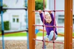 Милая маленькая девочка имея потеху на спортивной площадке outdoors в лете Стоковые Изображения RF