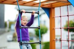 Милая маленькая девочка имея потеху на спортивной площадке outdoors в лете Стоковая Фотография