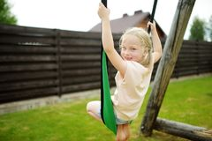 Милая маленькая девочка имея потеху на спортивной площадке outdoors в лете стоковое фото
