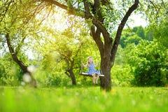 Милая маленькая девочка имея потеху на спортивной площадке outdoors в саде лета Стоковые Фотографии RF