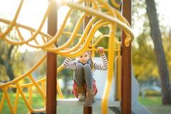 Милая маленькая девочка имея потеху на outdoors спортивной площадки в лете стоковое изображение