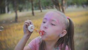 Милая маленькая девочка имея пузыри мыла потехи дуя в парке на солнечный день видеоматериал