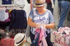 Милая маленькая девочка и ее бабушка выбирая одежды в магазине Стоковое фото RF