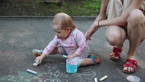 Милая маленькая девочка и ее чертеж матери с мелом на тротуаре на лете паркуют Семья, материнство и концепция людей видеоматериал