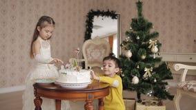 Милая маленькая девочка и положенные мальчиком сладостные снежинки на рождестве испекут красивые дети в просторном и светлой комн сток-видео