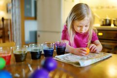 Милая маленькая девочка крася пасхальные яйца дома Яйца картины ребенка красочные для охоты пасхи Ребенк получая готовый для торж стоковое изображение rf