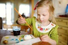 Милая маленькая девочка крася пасхальные яйца дома Яйца картины ребенка красочные для охоты пасхи Ребенк получая готовый для торж стоковая фотография rf