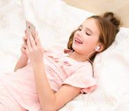 Милая маленькая девочка лежа на кровати и слушая к музыке используя s стоковые фото
