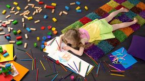 Милая маленькая девочка лежа на поле и рисуя с карандашами цвета на бумаге, искусстве стоковое фото