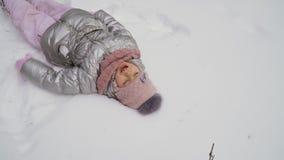 Милая маленькая девочка лежит на снеге сток-видео