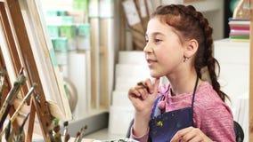 Милая маленькая девочка показывая большие пальцы руки вверх пока красящ изображение на художественном классе сток-видео