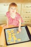 Милая маленькая девочка помогая ее матери печет печенья в кухне стоковые изображения rf