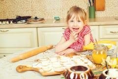 Милая маленькая девочка помогая ее матери печет печенья в кухне стоковые фотографии rf