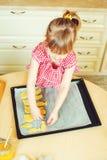 Милая маленькая девочка помогая ее матери печет печенья в кухне стоковые изображения