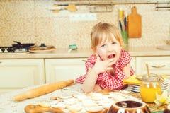 Милая маленькая девочка помогая ее матери печет печенья в кухне стоковые фото