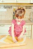 Милая маленькая девочка помогая ее матери печет печенья в кухне стоковая фотография