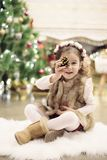 Милая маленькая девочка празднуя рождество дома Она сидит на стуле и держит елевый конус в ее руках взволнованности положительные стоковое фото