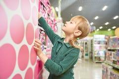 Милая маленькая девочка принимая игрушку от собственной личности в большом магазине стоковое фото